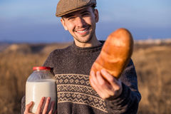 Man with bread and milk in a field Royalty Free Stock Photography
