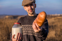 Man with bread and milk in a field Stock Photo