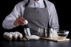 Man break egg in bowl. recipe of pie making on dark background stock photography