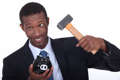 Man break into piggy bank. Man trying to break into a piggy bank with a hammer Royalty Free Stock Image