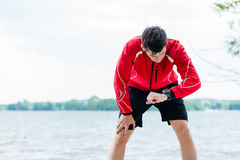 Man at break from running in front of lake Stock Image