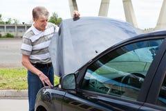 Man with breakdown car. Mature man opens car hood to repair breakdown in his car stock images