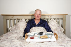Man with Breakfast in Bed Royalty Free Stock Images