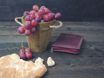 Man breaking the bread, with wine, grapes and Bible in the background.  royalty free stock photography