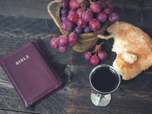 Man breaking the bread, with wine, grapes and Bible in the background.  stock photos