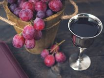 Man breaking the bread, with wine, grapes and Bible in the background.  royalty free stock photos