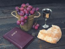 Man breaking the bread, with wine, grapes and Bible in the background.  royalty free stock photo