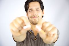 Man breaking cigarette in two pieces Stock Images