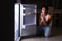 The man breaking diet at night near fridge. Man breaking diet at night near fridge royalty free stock photos