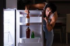 The man breaking diet at night near fridge. Man breaking diet at night near fridge stock image