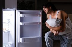 The man breaking diet at night near fridge. Man breaking diet at night near fridge royalty free stock images