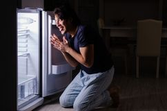 The man breaking diet at night near fridge royalty free stock photography