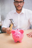 Man breaking piggy bank with hammer Stock Image
