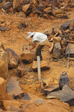 Man breaking rocks. Worker breaking rocks with hammer and chisel in a stone quarry Stock Photography