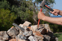 Man breaking rocks. Man with mallet and chisel breaking rocks Royalty Free Stock Photography