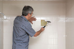 Man breaking up tiles Stock Photo