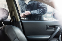 Man breaks into a car. Inside view of it as a man breaks into a car stock photography