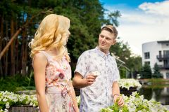 Man breaks a flower and give to his girlfriend. Man breaks a flower and give to his blond girlfriend Stock Images