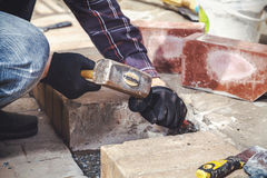 Man breaks masonry hammer and chisel. Hands in gloves men destroy the brick steps with a hammer and a chisel close-up royalty free stock photo