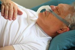 Senior man asleep wearing CPAP device stock photo