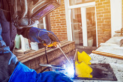 Man brewing a metal welding machine. Man welder wearing a welding mask, building uniform and blue protective gloves brewing a metal welding machine on a street Stock Images