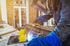 Man brewing a metal welding machine. Man welder wearing a welding mask, building uniform and blue protective gloves brewing a metal welding machine on a street Stock Image