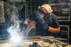 Man brewing a metal welding machine. A young bald man in a welding black mask and black T-shirt brews a metal  arc welding machine  construction in a dark Stock Photos