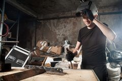 Man  brews a metal. An adult man welder in a black T-shirt and a black welding mask brews a metal welding machine in a dark workshop Royalty Free Stock Images