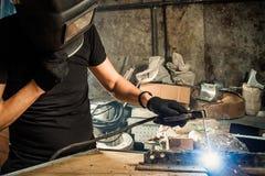Man  brews a metal. An adult man welder in a black T-shirt and a black welding mask brews a metal welding machine in a dark workshop Stock Photos