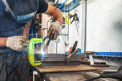 Man brews a metal. A strong man in a welding mask and working clothes brews a metal angle with a welding machine on a wooden table in the factory, blue sparks Stock Image