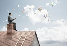 Man on brick roof reading book and aerostats flying in air Royalty Free Stock Image