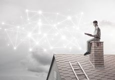 Man on brick roof reading book and concept of social connection stock image