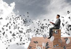 Man on brick roof reading book and symbols flying around. Young businessman sitting on house with red book in hands Stock Images