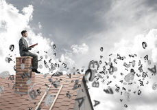 Man on brick roof reading book and symbols flying around Stock Photography