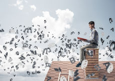Man on brick roof reading book and symbols flying around Royalty Free Stock Image