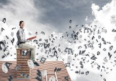Man on brick roof reading book and symbols flying around. Young man in casual sitting on house with red book in hands Stock Photography