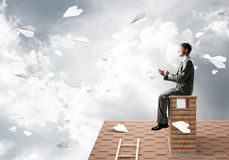 Man on brick roof send message with smartphone and paper planes flying in air Royalty Free Stock Photography