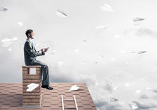 Man on brick roof send message with smartphone and paper planes Royalty Free Stock Images