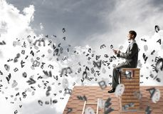 Man on brick roof working with smartphone and symbols flying around. Young businessman sitting on house with smartphone in hands Stock Photos