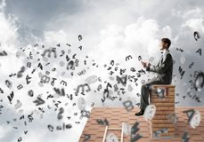Man on brick roof working with smartphone and symbols flying around. Young businessman sitting on house with smartphone in hands Royalty Free Stock Image
