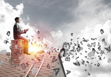 Man on brick roof working with smartphone and symbols flying around Royalty Free Stock Images