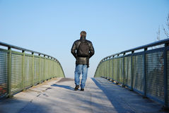 Man on bridge. Man walking on bridge, image taken from behind, no face visible Stock Photo