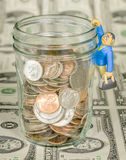 Man with briefcase hang from jar of coins Royalty Free Stock Photography
