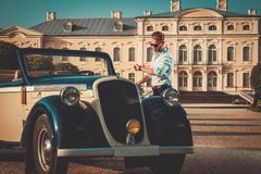 Man with briefcase near classic convertible. Confident wealthy young man with briefcase near classic convertible Royalty Free Stock Image