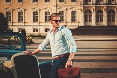 Man with briefcase near classic convertible Stock Photo