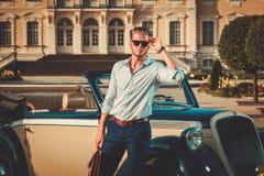 Man with briefcase near classic convertible Stock Photos