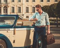 Man with briefcase near classic convertible Royalty Free Stock Image