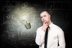 Man and bright bulb over icons background. Thoughtful man near bright bulb over icons on chalk board Royalty Free Stock Photo