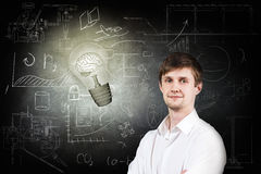 Man and bright bulb over icons background. Thoughtful man near bright bulb over icons on chalk board Stock Images