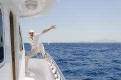 A man in bright clothes wearing a cap and glasses on a yacht. Is happy to leave.Copy space Royalty Free Stock Image